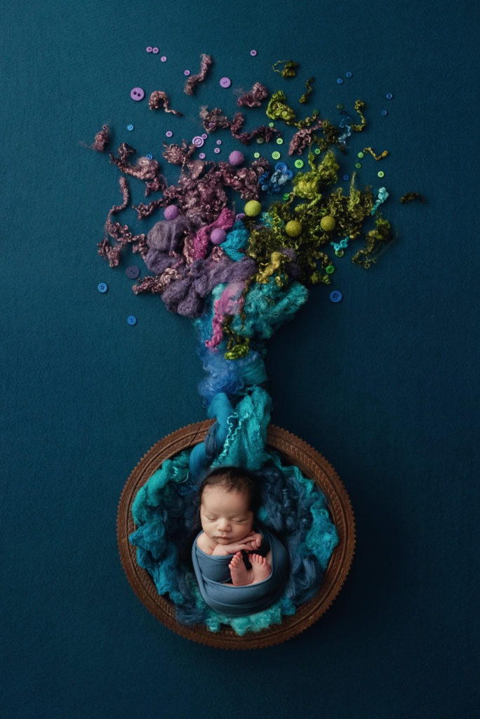 Baby wrapped in blue in a purple green and blue tree setup