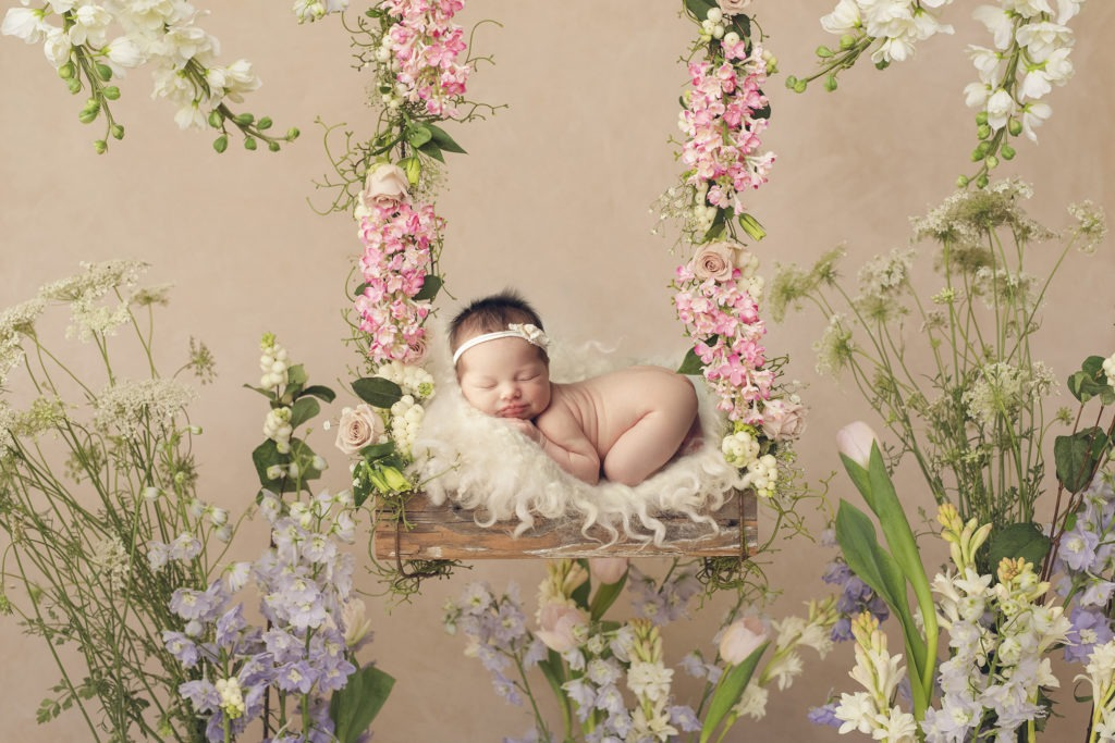 Baby laying on swing with flowers surrounding her