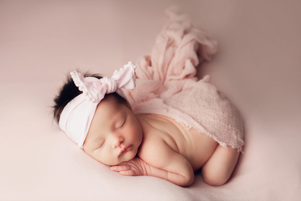baby laying on stomach with a wrap covering her bum. her hand is under her cheek