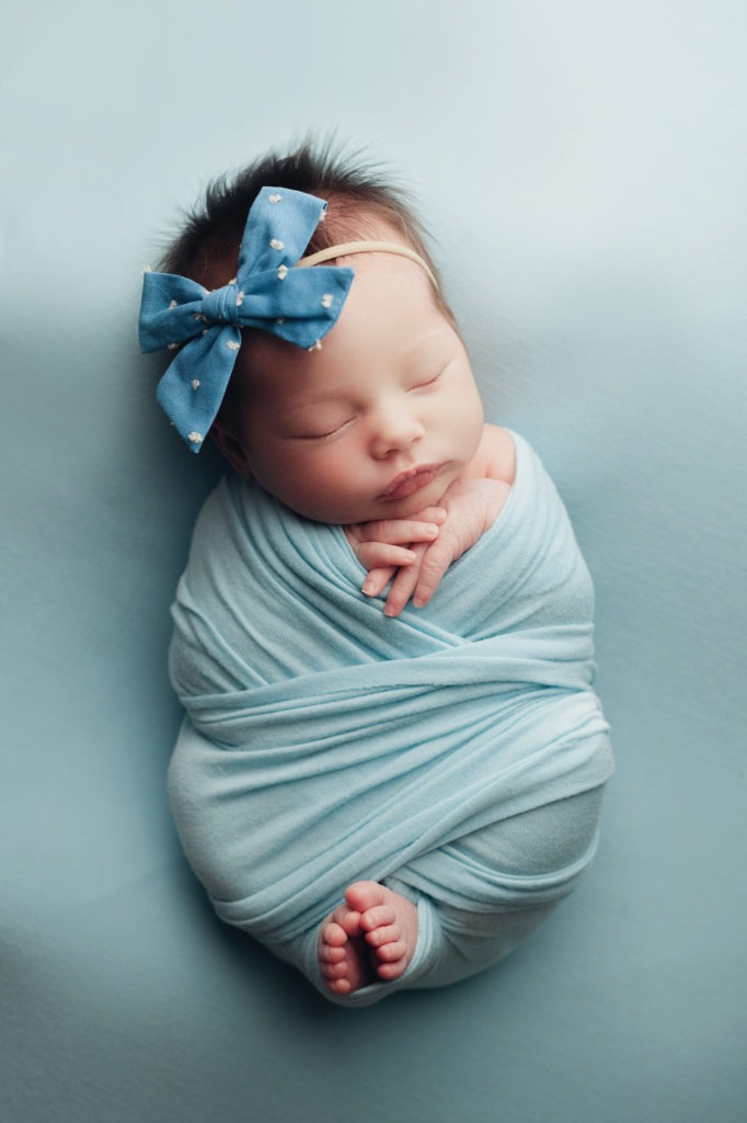 baby in a baby blue criss cross wrap