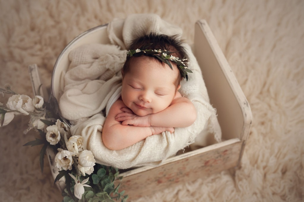 baby laying in a bucket with flowers smiling