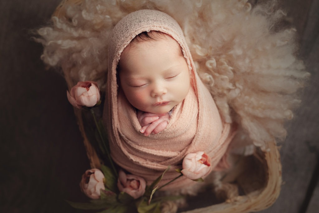 baby wrapped up in a basket with flowers