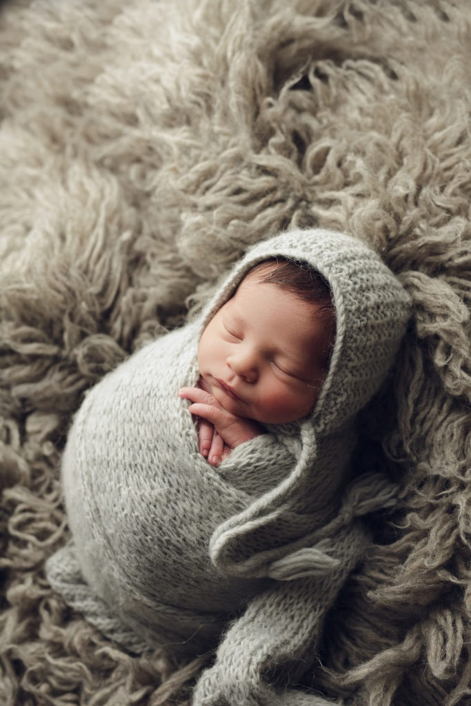 newborn boy wrapped up on grey with a bonnet