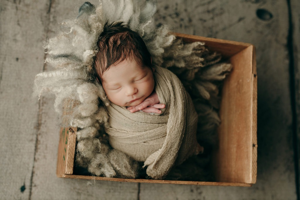 newborn boy sleeping wrapped up in a tan colored crate