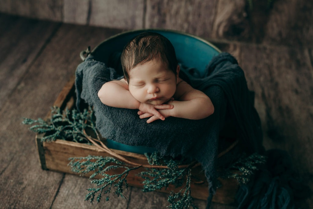 newborn boy sleeping in a blue bucket