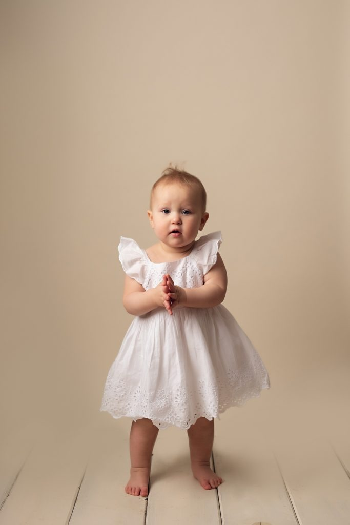 baby standing on white wood with white dress