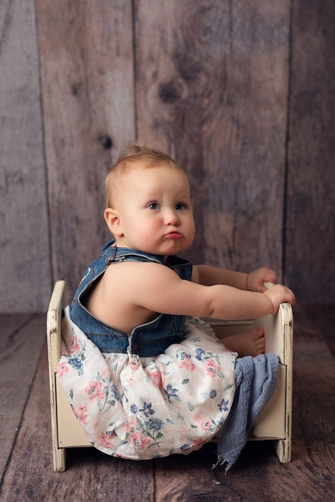 baby sitting in bed on wood backdrop