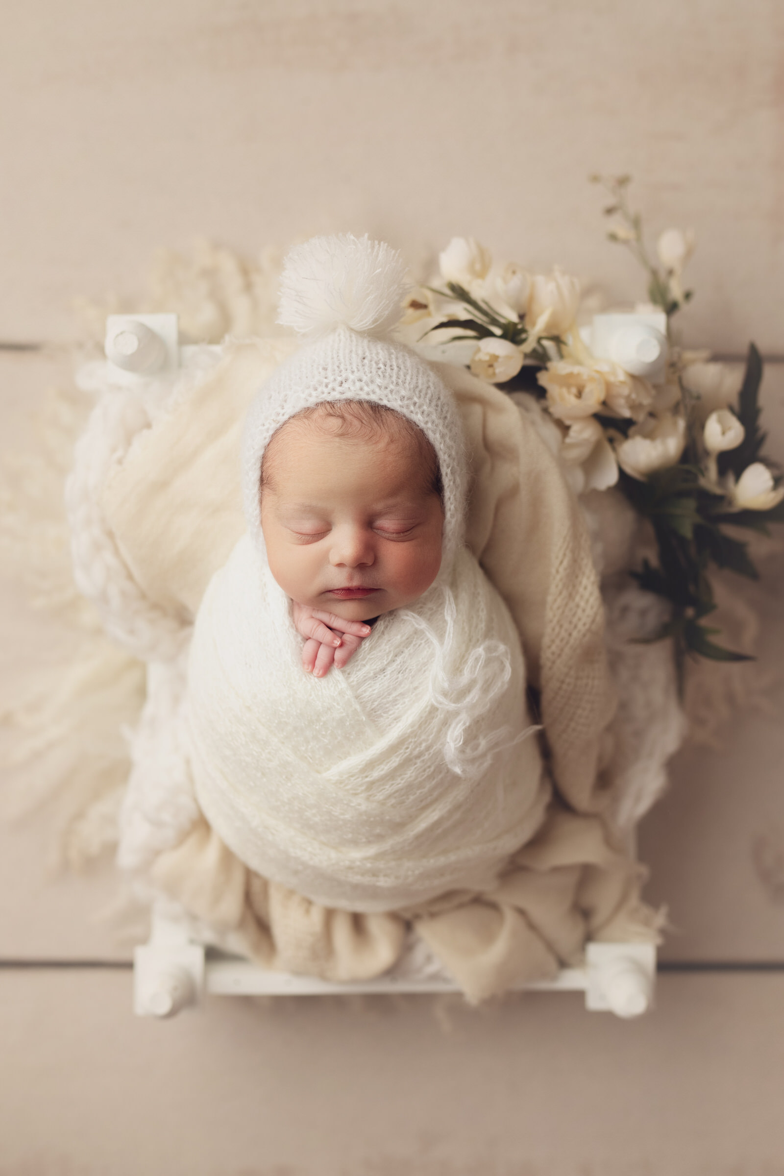 Baby sleeping face up on a white bed with flowers