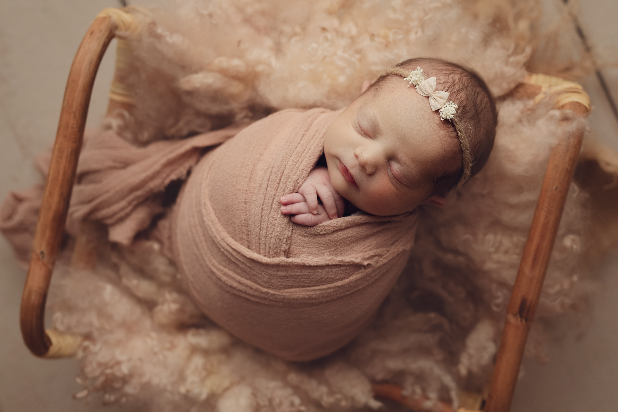 baby laying in pale pink fluff with headband