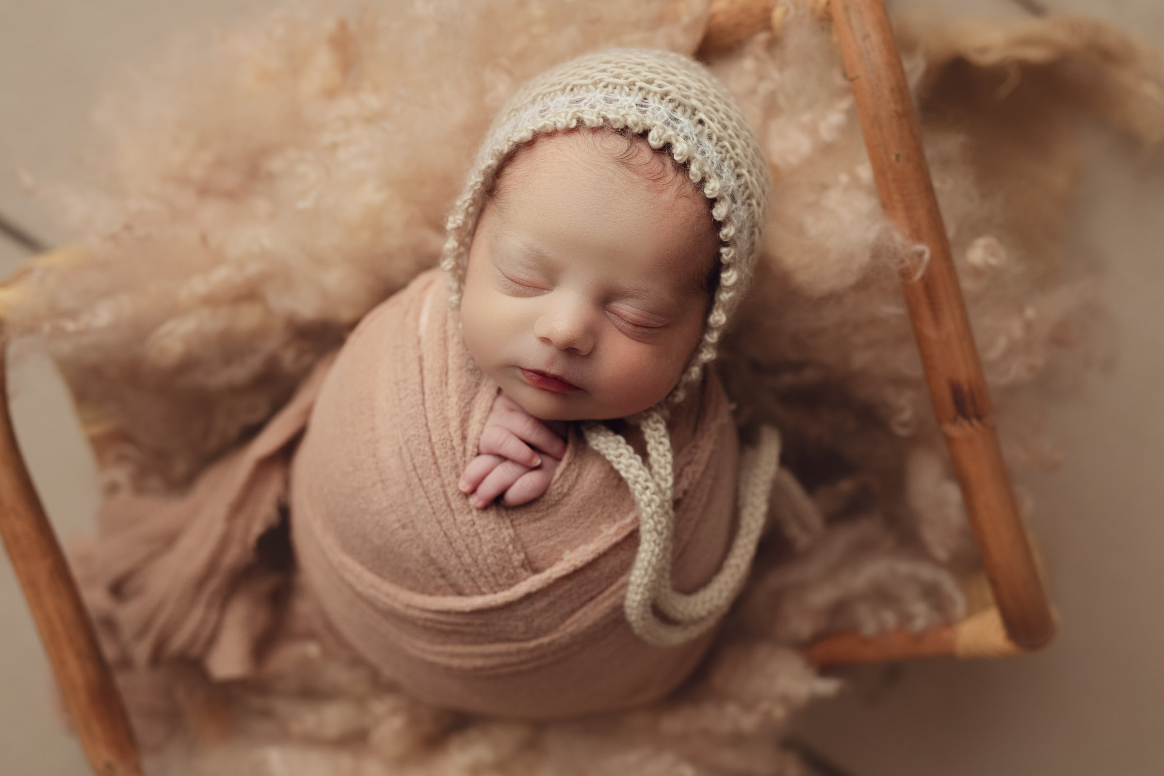 baby laying in pale pink fluff wrapped up with bonnet