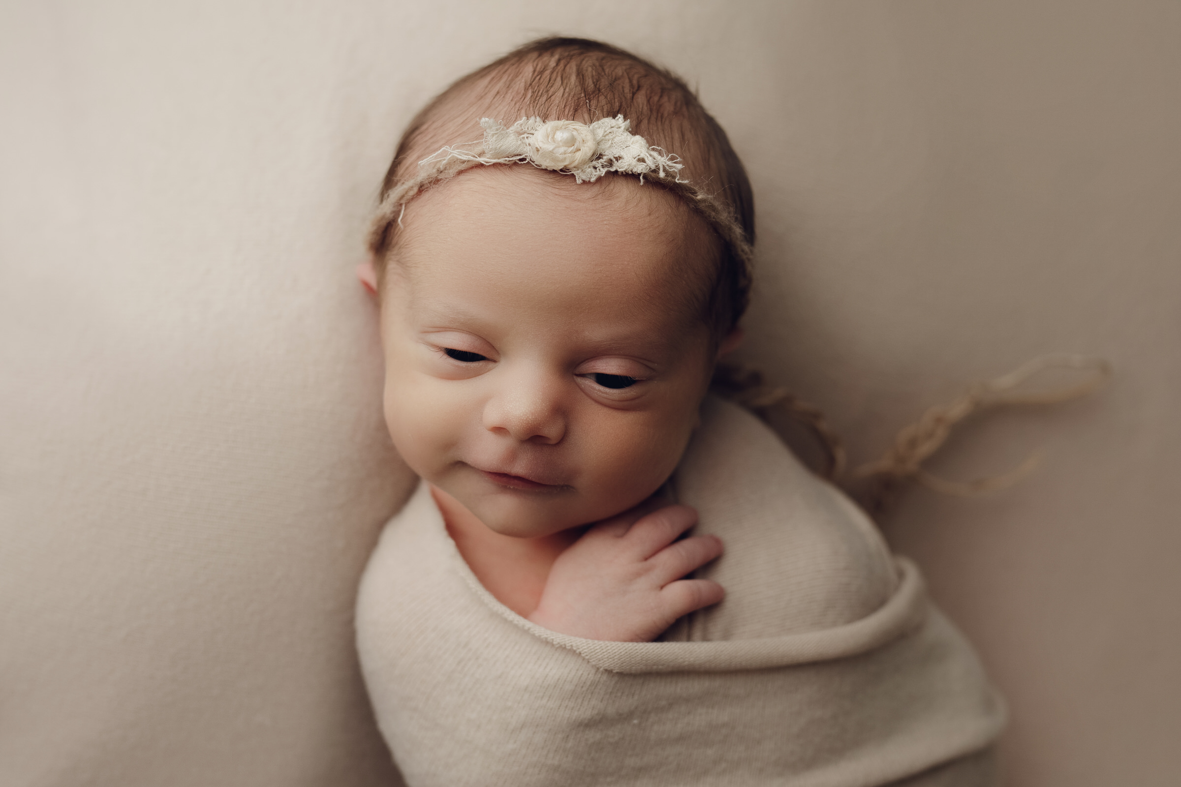 baby wrapped up awake and smiling