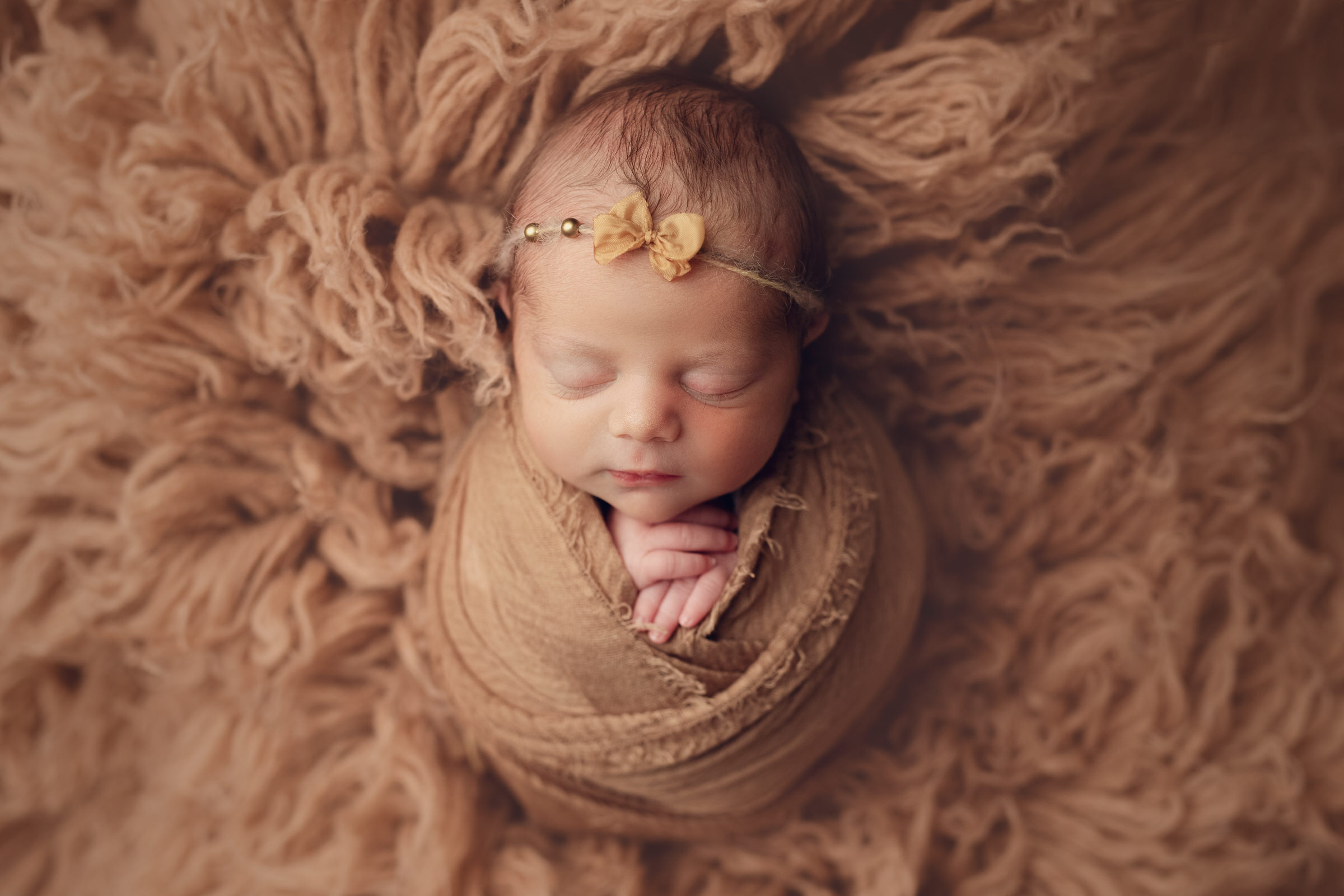 baby wrapped up on brown fur rug