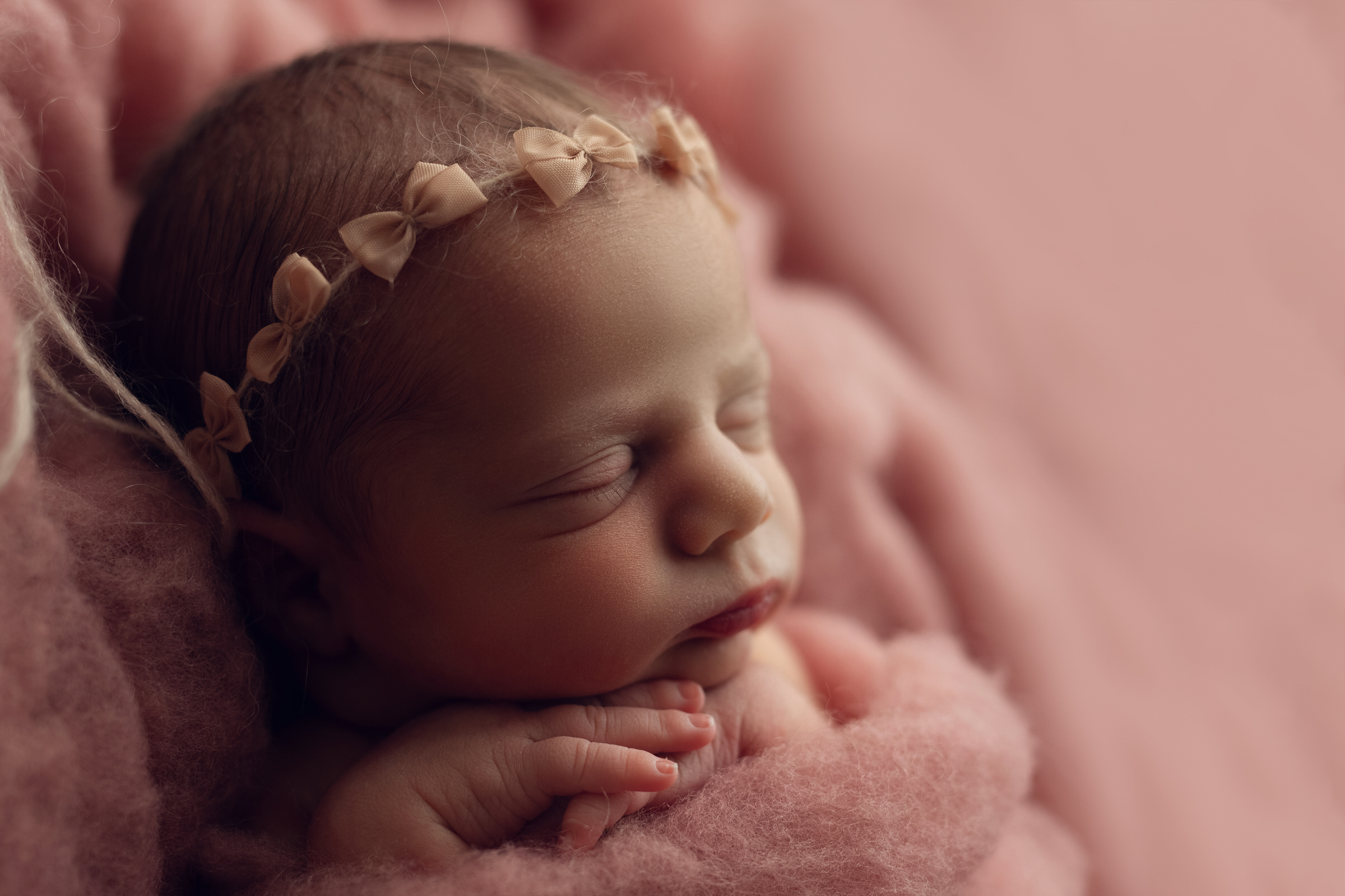 side view of baby's profile on pink backdrop